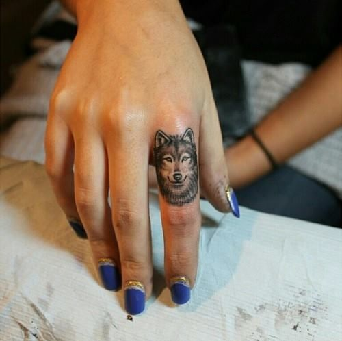 Finger tattoo. Maybe not a wolf but cool placement that looks amazing for how small it is