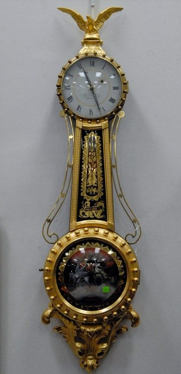 Elmer Stennes girandole clock in the manner of Curtiss, weight driven, top with gilt eagle finial, gilt trimmed bowed throat glass - Realized Price: $4,887.50
