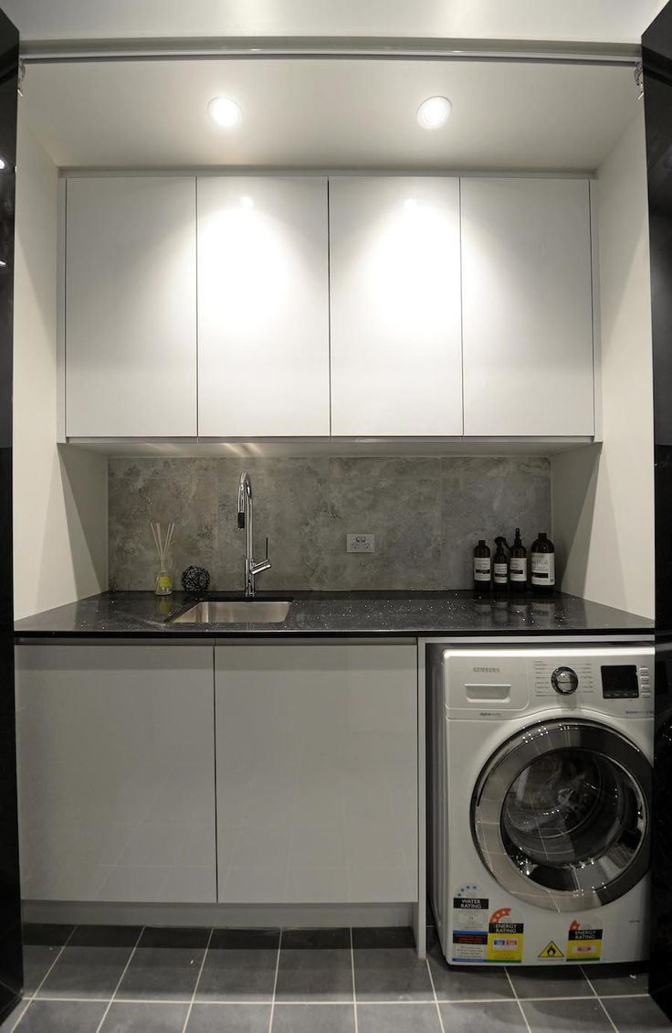 White laundry with black bench top and grey tiled floor. See more photos at stylecurator.com.au now