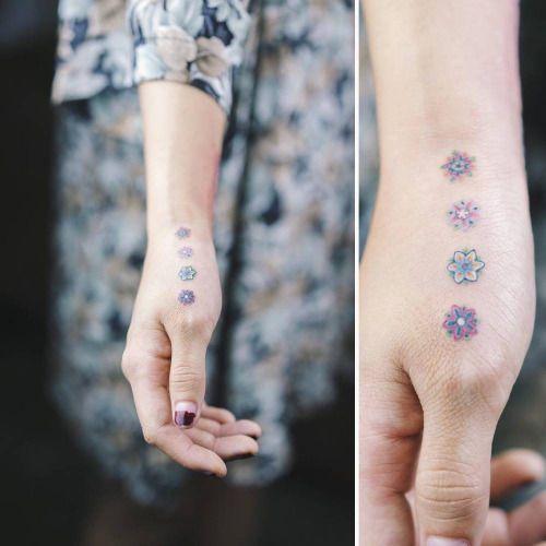 Tatuaje de cuatro pequeñas flores de colores en la mano derecha....