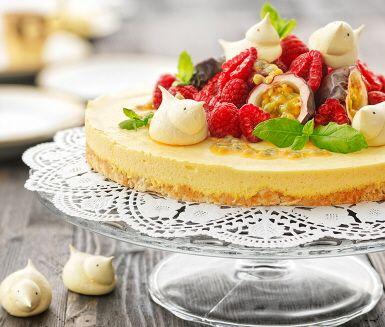 En glutenfri tårta med härlig smak av kokos och mango. Botten blir stadig med äggvitor och kokosmjöl, och täcks av en len mangomousse. Garnera tårtan med hallon, passionsfrukt och mynta – vackert!