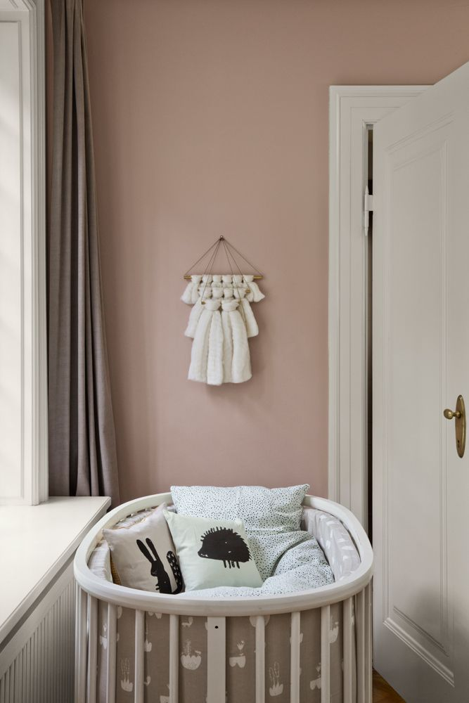 Ferm Living created a nursery styling with simple furniture and subtle pink walls. This is a relaxing tone that adds warmth to the room and can be a wonderful option for a calming nursery.