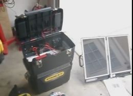 Homemade solar-powered auxiliary power system constructed from a 125AH deep-cycle marine battery, a 10-ampere MPPT charge controller, a 750W inverter, a float charger HF, and a 12v fan, all housed in a plastic portable toolbox. A folding solar panel is utilized to charge the battery