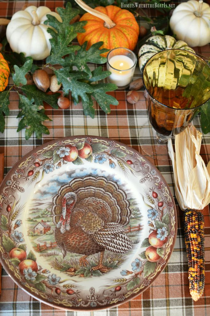 Thanksgiving table with assorted turkey plates, plaid tablecloth and easy centerpiece with pumpkins, oak leaves, nuts and votives | homeiswheretheboatis.net--Royal Stafford