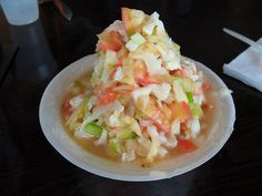 Conch (Bahamas). 'Popular conch dishes include cracked conch (battered and fried), conch salad (chopped and tossed with onions, tomatoes and lime juice), conch fritters (deep-fried balls of minced conch and batter) and conch chowder.' http://www.lonelyplanet.com/the-bahamas