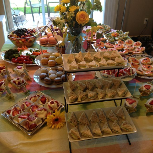 Cucumber tea sandwiches, individual strawberry shortcakes, macaroons, fruit Now THIS is an afternoon Tea! salad, bagels with flavored cream cheese, and cookies like pepperidge farms Milanos or chessmen dipped in chocolate   All on platters or trays on white table cloth