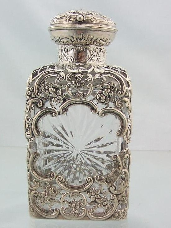 "Cut glass perfume scent bottle with silver overlay, by William Comyns. Hallmarks are for London 1897. 6"" tall and 2.5"" square."