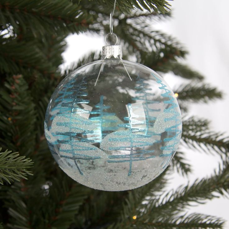 Luxurious and decorative glass Christmas bauble, 10cm, transparent with ice blue pine trees. Mouthblown and decorated by hand. A very exclusive European product, and a true eye-catcher for your Christmas tree.
