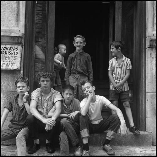 Children at an apartment entrance. Chicago, 1965.  By Danny Lyon