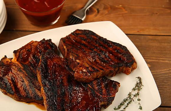 Grilled Delmonico steaks: Coated with a spicy rub and mopped with sauce, this version makes a great summer meal.