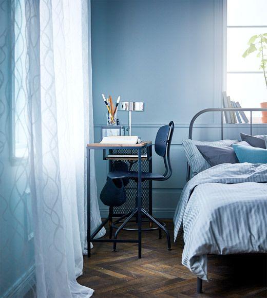 Schlafzimmer mit FJÄLLBO Laptoptisch schwarz auf Rollen mit einem Drehstuhl im Raum zwischen Bett und Wand