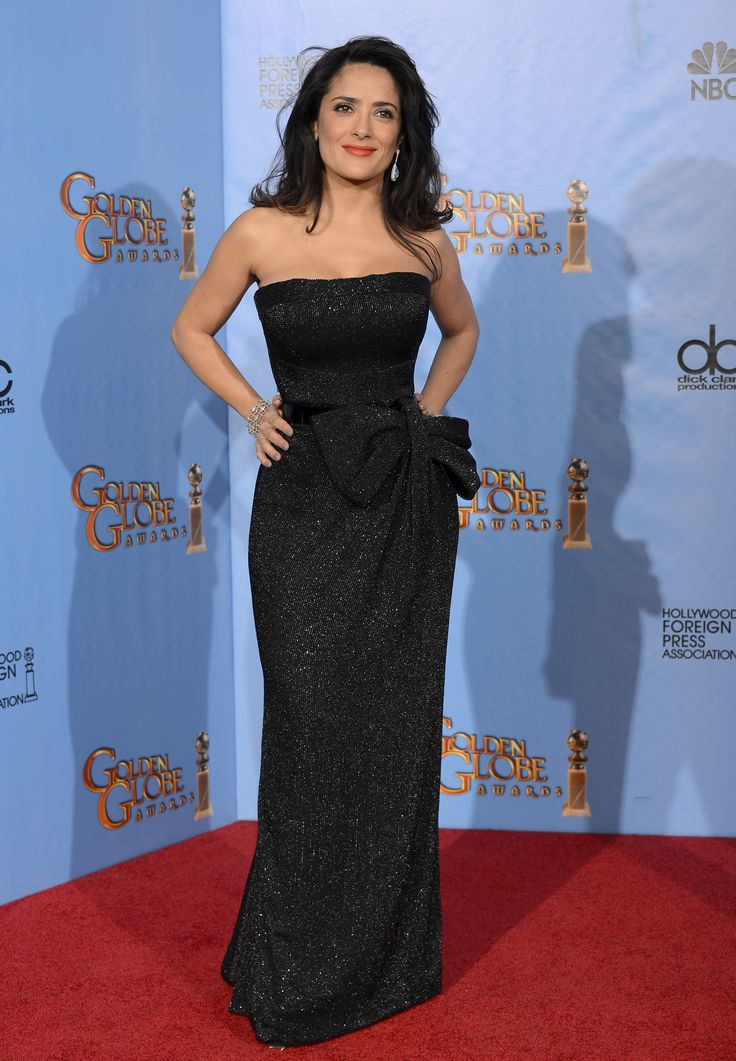 Presenter Salma Hayek-Pinault wore a Gucci Première midnight blue silk georgette strapless gown fully embroidered with micro glass beads and with a black patent leather belt and fully beaded oversized bow detail at the waist and black satin clutch to the 70th annual Golden Globe Awards in Los Angeles, California.