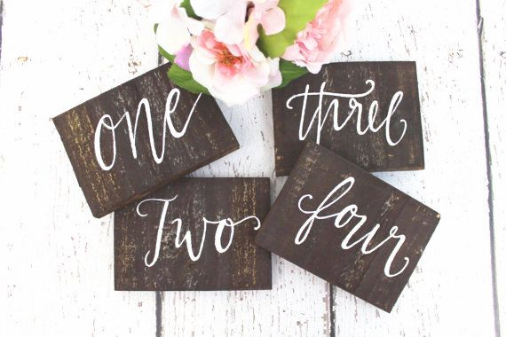 """Free standing recycled barn wood table numbers with white calligraphy script. Size: Length 6″ – Width 4″ – Thickness .5″ . Also have """"Gifts & Cards"""" sign and """"Mr."""" and """"Mrs."""" signs – same size and style."""