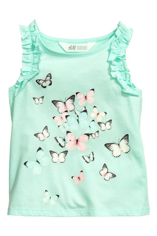 Sleeveless top in cotton jersey with a print motif on the front and frill trims around the armholes.