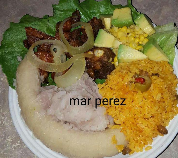 Arroz con gandules, carne de cerdo frita, viandas, guineo hervido y ensalada de maíz, lechuga y aguacate