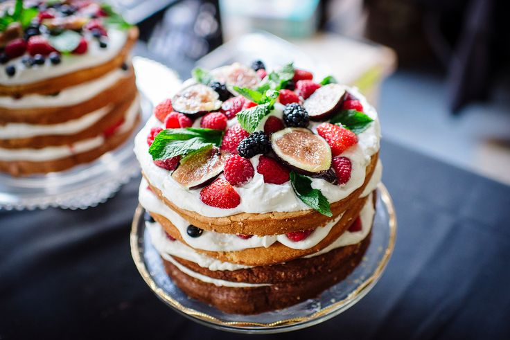 Wedding cakes with layers of a light vanilla cake with anise-flavored whipped ricotta, fresh berries, figs, and mint leaves.