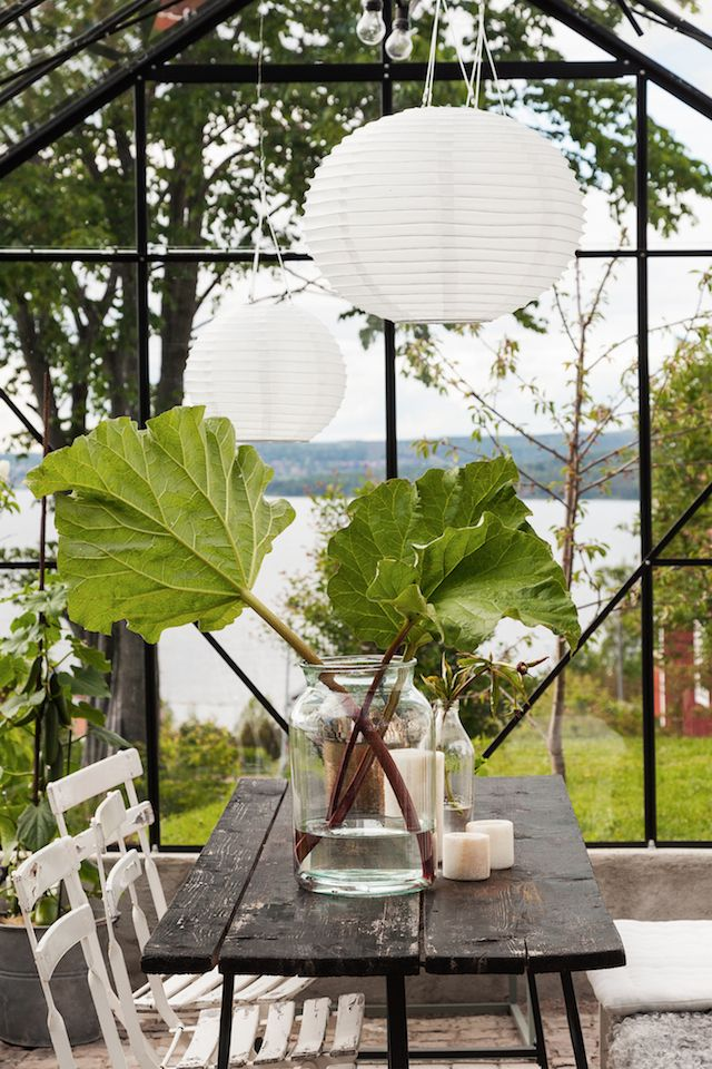 Greenhouse in the garden of a Swedish home on a hill with lovely lake views