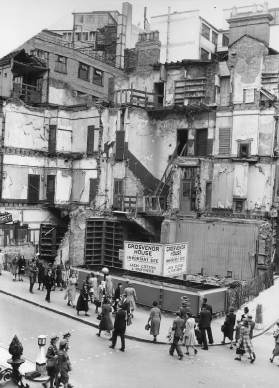 People walk past a large bomb site on the corner of New Street in Birmingham, England. A large notice states that this 'important site' is to be reserved for the building of Grosvenor House, when conditions permit. Three members of the Women's Auxiliary Air Force (WAAF) can just be seen in the foreground.
