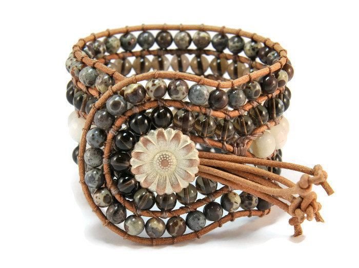 A 5 strands women's bracelet is handcrafted with semi precious stones of jasper, moon stone & smoky quartz. All of them are framed by natural brown leather woven together with brown cotton cord. This easy - to - wear design also features a metal, lightly bronze, vintage, flower closure. This gorgeous bracelet pairs beautifully with other gold or silver tone pieces, but can also make a subtle shimmering statement worn alone.