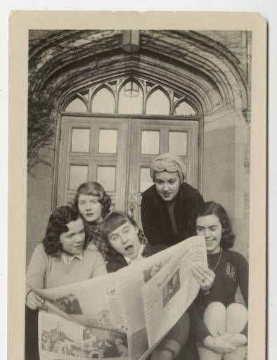 Group of students, l-r, Marjorie (Marge) Marshall x51, Priscilla (Prill) Stein '50, Jennifer Pyne x'51, Joan Redin '51, and Joan Bagley '51 sharing a newspaper on the steps of South Manelle Hall :: 1947 :: MHC Archives and Special Collections Digital Images