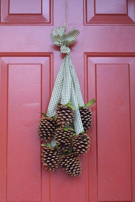 Décoration suspendue pour la porte à Noël avec pommes de pin et ruban