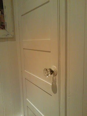 Add MDF to a plain hollow core door to give it a paneled look. Now paint everything white!.