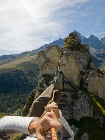 Stock Photo : Climber crosses gap on rope traverse, ridgeline