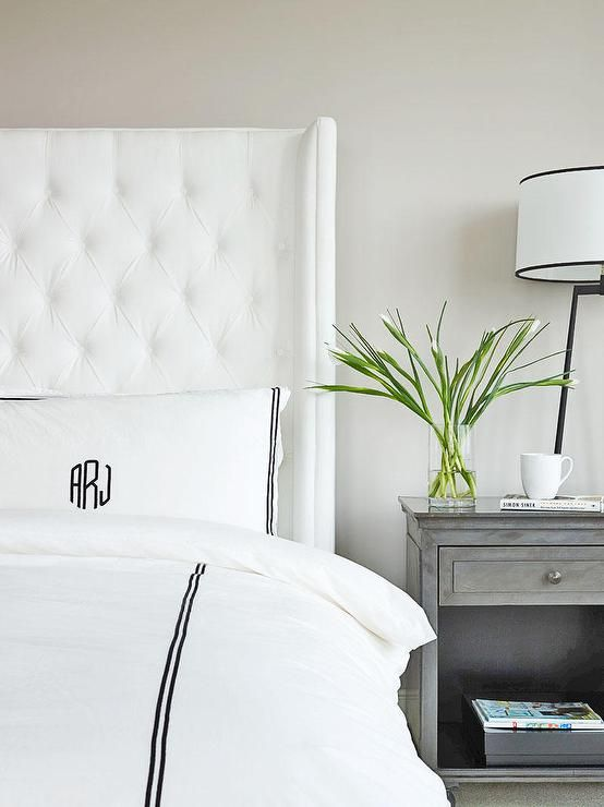 Exquisite bedroom features a white tufted wingback bed dressed in a black and white hotel duvet ...
