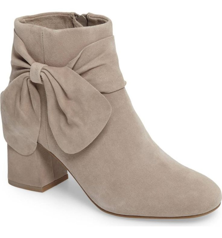 An oversized bow embellishes the side of a fashion-forward bootie grounded by a bold block heel.