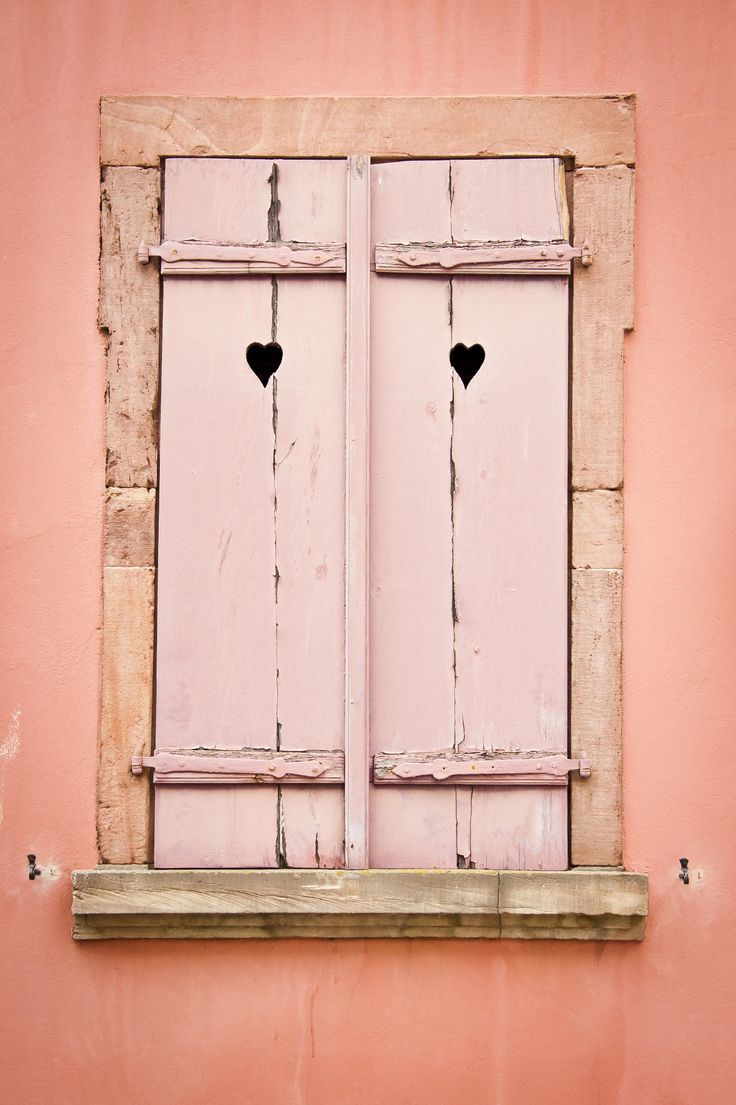 Closed pink wooden shutters with heart shape cutouts on pink wall.