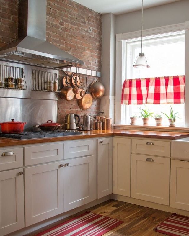 Flirty florals mix with delicate Asian influences, which balance out sturdy wooden furniture and powerful architecture. Bright red gingham curtains in the kitchen contrast yet complement industrial and rustic elements.