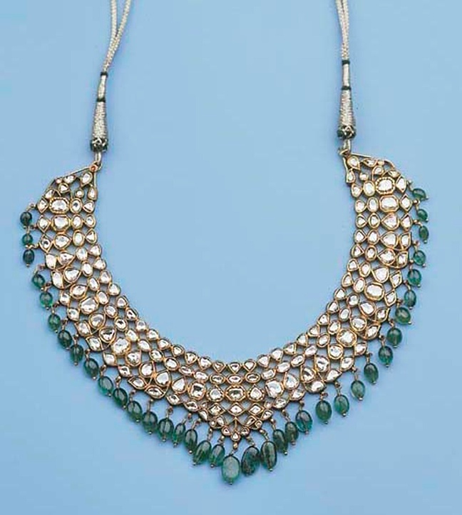 an indian gold necklace set with diamonds and emeralds The half-moon shaped necklace with four rows of tear-drop shaped beads set with diamonds, suspending a row of emerald beads, the reverse enamelled with green, red and white flower heads circa 16 cm wide