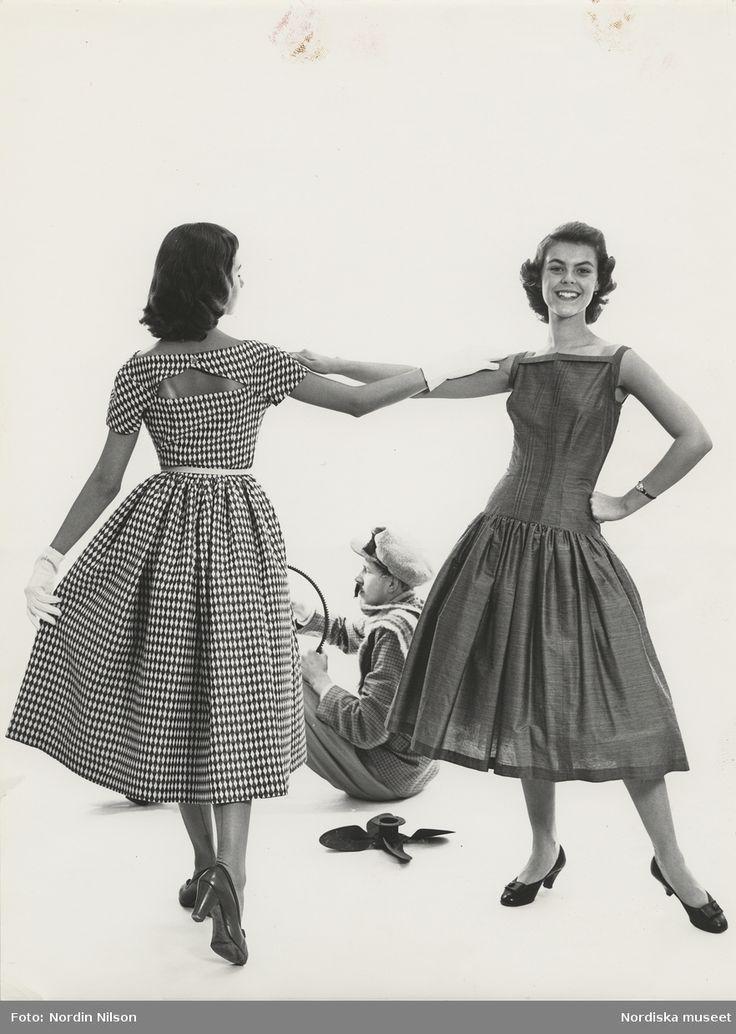Två modeller i klänningar håller om varandras armar. Klänningar från Wahls 155:- och 98:- Modell i keps och kavaj sitter ned på golvet. Fotograf: Nordin/Nilson, 1955.