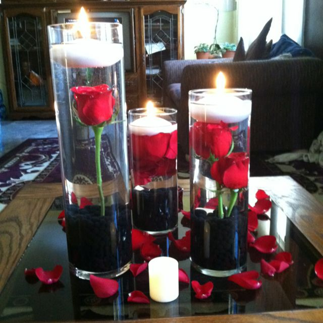 Red roses with white floating candles and black rocks at the bottom. Super cute centerpieces. Pretty!