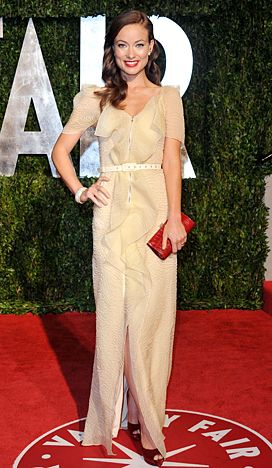 Olivia Wilde's Most Stunning Red Carpet Moments: Classic Beauty in a pale yellow RM by Roland Mouret gown with glossy retro waves and vibrant red lips at the 2010 Vanity Fair Oscar Party.