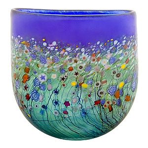Inspired by lush meadows and the emergence of spring blossoms, beautiful millefiore flowers decorate each Large Flat Crucible Vase. Shown in Cobalt and Emerald with multi-colored murrine. Off-hand blown glass using house-made murrini, frits and stringers. Iridescent surface and diamond-polished finishing. Each piece is signed by the artist. Clean with damp cloth. Each piece is unique. Slight variations in coloration and patterning may occur.