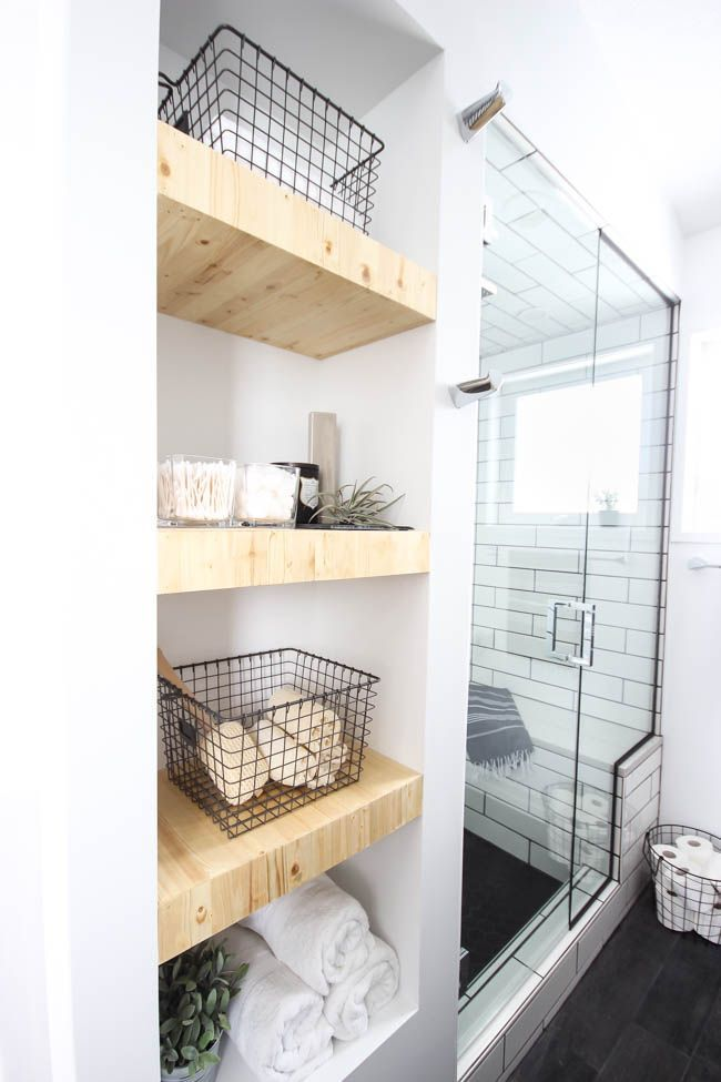 A beautiful modern bathroom renovation with chrome and matte black faucets, sleek modern fixtures and natural wood accents. Beautiful transformation!  Subway tile with black grout, wood grain tile,  natural wood accents, industrial chic, built-in natural wood shelving, floor to ceiling shower glass
