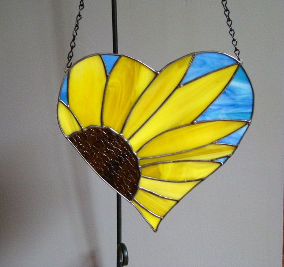 This stained glass sunflower heart panel will bring spring into your home. It measures 10-1/2 x 10-1/2 inches  Made with yellow and brown glass with a bit of blue to represent the sky. Created via the copper foil technique.