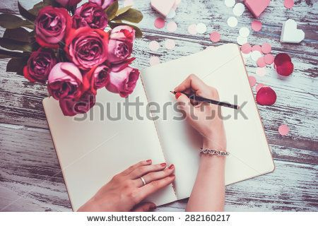 Female hands writing in open notebook and bouquet of roses on old wooden table. Top view. Toned image