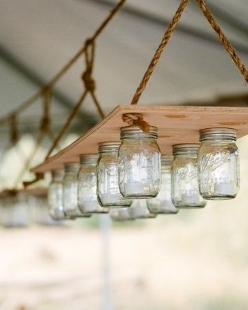 Mason jars can become a simple hanging light. To illuminate the tented space, Lyn and Luke crafted hanging candelabras from one-foot-wide plywood boards, rope, and Mason jars. They filled each jar with an electric tea-light candle. The soft glow set the dinner and seating area apart from the dance floor and gave the tent a cozy, warm feel.