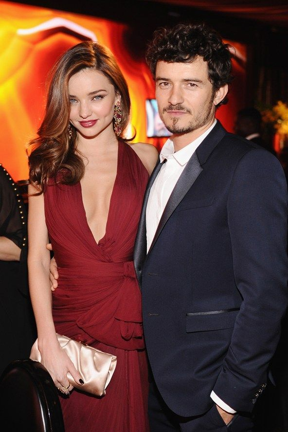 Miranda Kerr wearing a plunging red dress to attend the Warner Bros Golden Globes after-party with husband Orlando Bloom