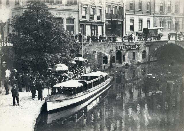 """Afbeelding van de eerste tocht van een rondvaartboot (""""Watertram"""") te Utrecht, tijdens het aanleggen bij het terras op de werf van de Raadskelder bij de Stadhuisbrug.  N.B. De Watertram was een initiatief van rederij J.H. Bergman uit Amsterdam in samenwerking met de V.V.V. Utrecht. 1932-1935"""