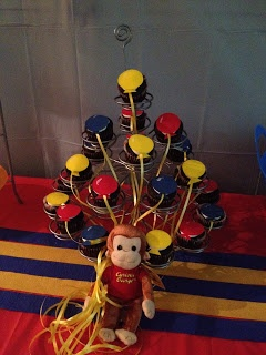 Cricut balloons on cupcakes w/ string attached down to a curious George stuffed animal?