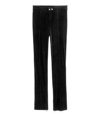 Donkerrood. Een broek van elastisch fluweel met een hoge taille en smalle, extra lange pijpen met een blinde rits onderaan. De broek heeft ingestikte