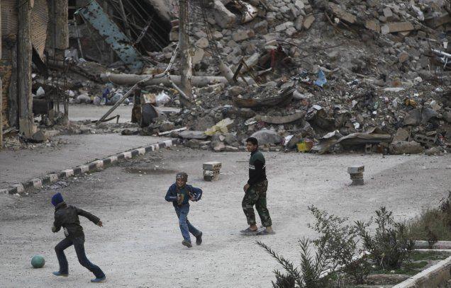 footynions:  Children play football in a damaged street in Deir al-Zor, eastern Syria.