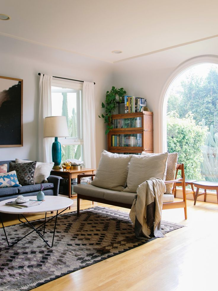 Love this open and airy midcentury styled living room with a geometric diamond print area rug, midcentury wood loveseat, dark gray tufted sofa with mixed seasonal throw pillows, colorful table lamp, and wood bookshelf topped with an indoor potted ivy plant.