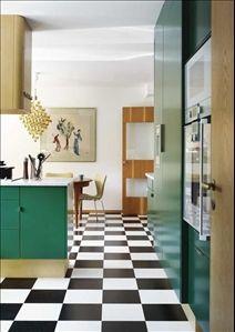 Nytt och original i förening. Schackrutig bas med golv-plattor i linoleum, Pergo golv. T h kyl och frys med inbyggd ismaskin bakom gröna trädörrar, samt inbyggd  ugn och mikro. Salt- och pepparkvarn i teak, NK  Glas, porslin & kök, vas, Holmegaard, köksredskap, Eva trio. Matbordet i teak är från 1960-talet, Gamla lampor, Sjuanstolar i original med tyg, design Arne Jacobsen, Deconet.com. På väggen en litografi av Salvador Dali.