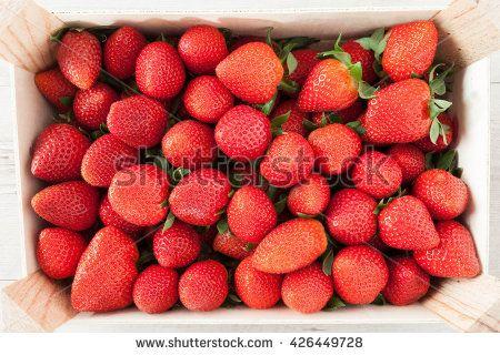 Fresh strawberries in wooden crate, top view shot