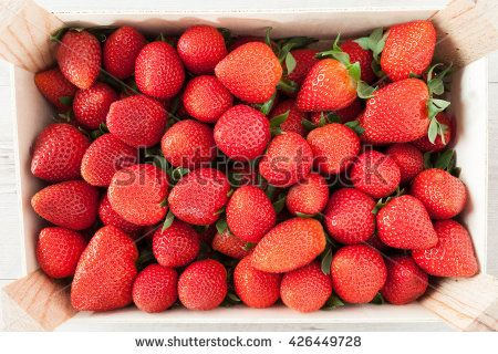 Fresh strawberries in wooden crate, top view shot