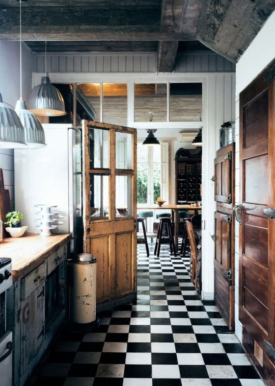 Kitchen with wood accents, chrome details, and black & white tiles.